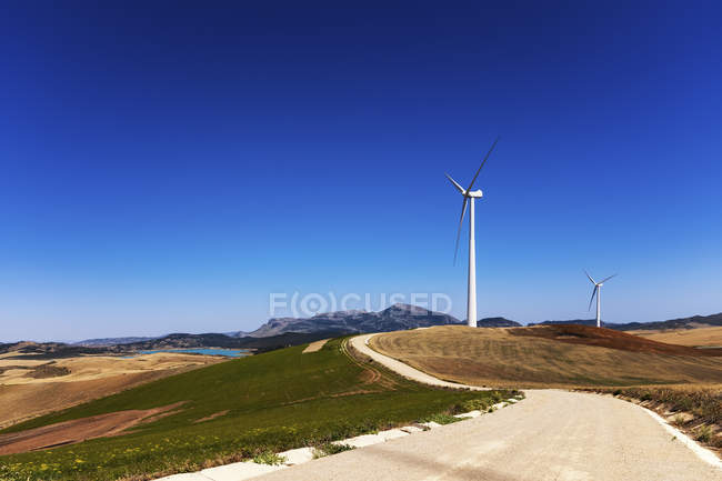 Spain, Andalusia, Wind turbines, country road and fields during daytime — Stock Photo