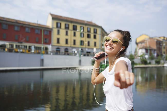 Молода жінка в навушники з smarthone в riverside в Яскраве сонце — стокове фото