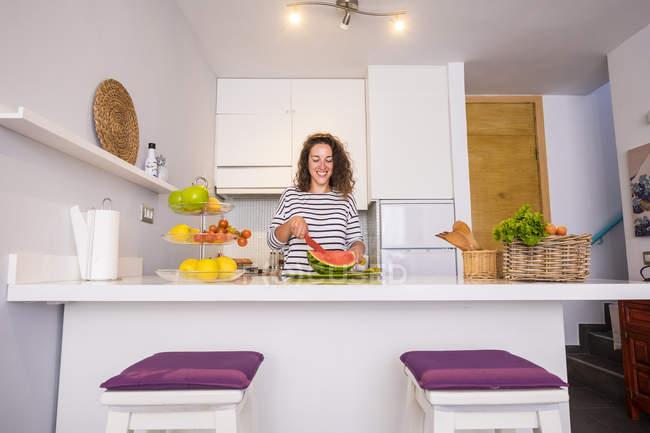 Mulher sorridente parado o kitche melancia de corte — Fotografia de Stock