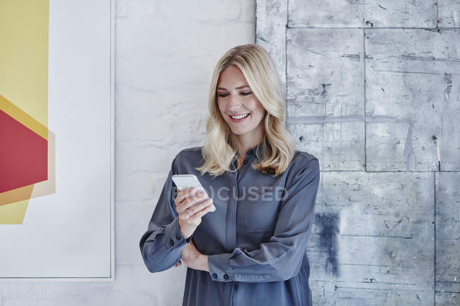 Smiling businesswoman looking at smartphone at modern office — Stock Photo