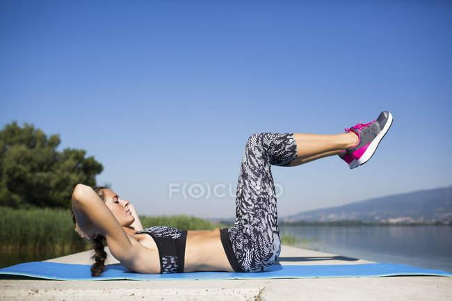 Mujer joven haciendo ejercicio en el lago - foto de stock