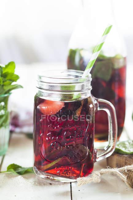 Thé glacé avec des fruits, hibiscus, fraises, menthe, citrons verts — Photo de stock