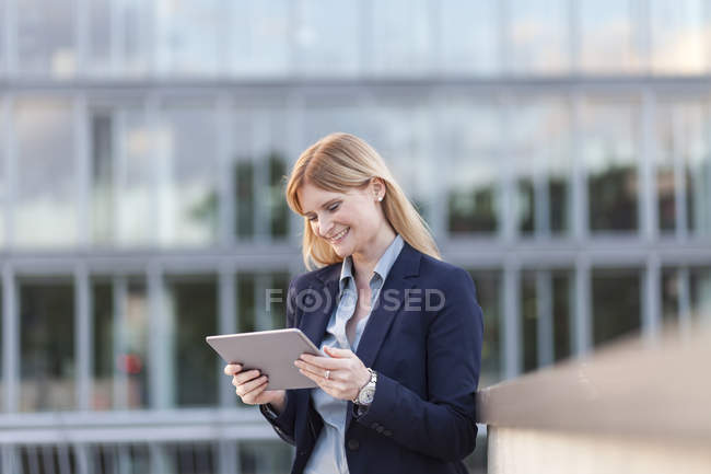 Smiling businesswoman looking at tablet — Stock Photo