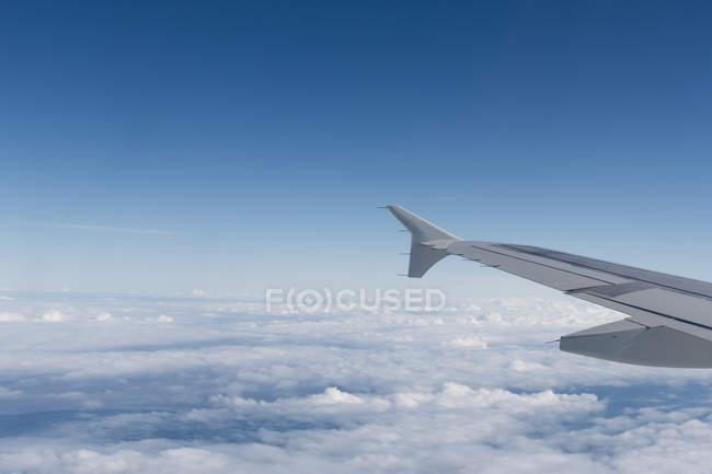 Asa de um avião com nuvem no céu — Fotografia de Stock