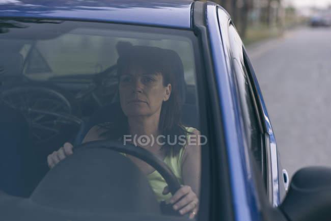 Portrait d'une femme sérieuse, conduire une voiture — Photo de stock