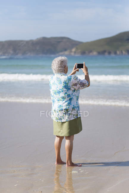 Back view of senior woman on the beach taking picture with smartphone — Stock Photo