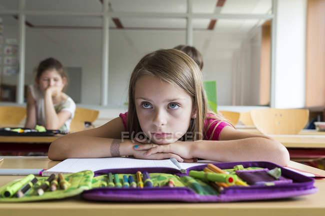 Retrato de colegial entediada sentada na aula — Fotografia de Stock