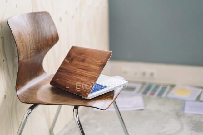 Wooden ноутбук на стуле в комнате — стоковое фото
