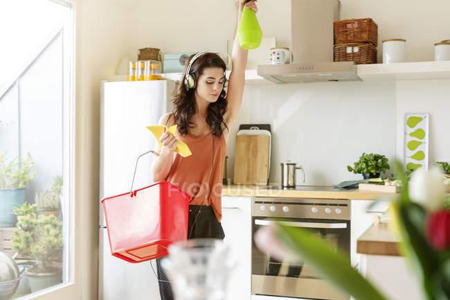 Молода жінка кухні прибирання та прослуховування музики — стокове фото