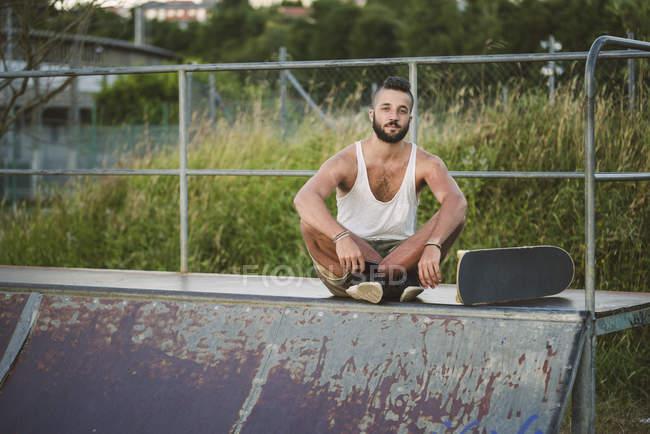 Porträt der Skateboarder sitzen auf Rampe im skatepark — Stockfoto