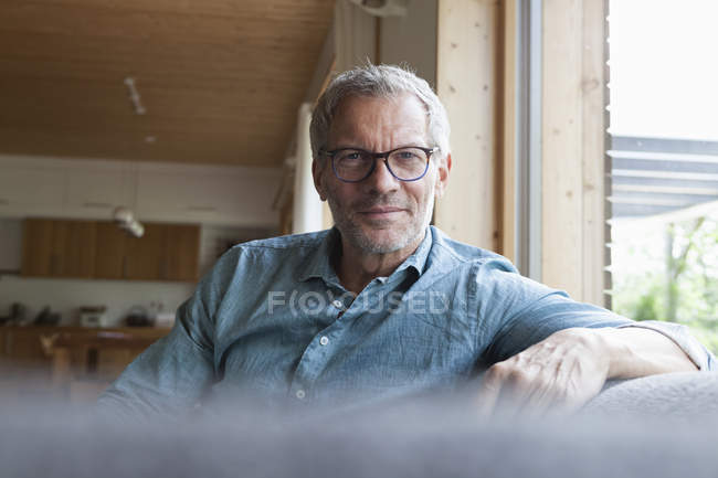 Retrato de homem maduro confiante sentado no sofá — Fotografia de Stock
