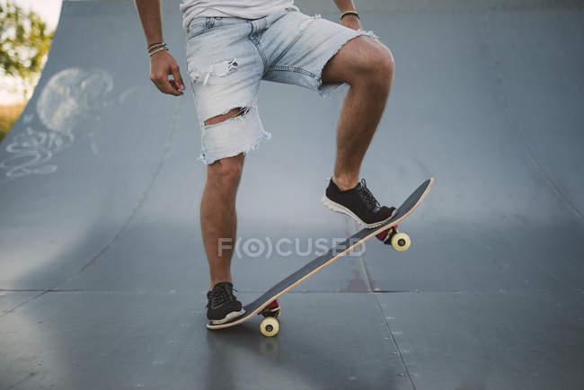 Legs of skateboarder on ramp in skatepark — Stock Photo