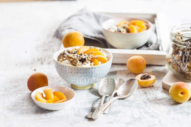 Joghurt mit knusprigen Müsli und frischen Aprikosen in Schüssel auf Holztisch mit Zutaten — Stockfoto