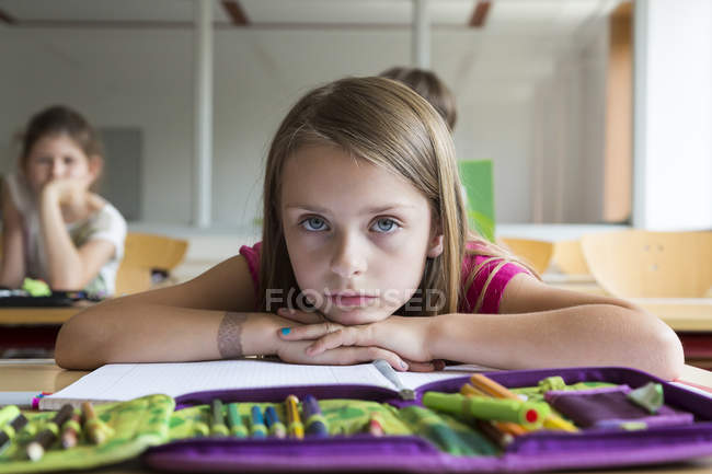 Portrait of bored schoolgirl sitting at class — Stock Photo
