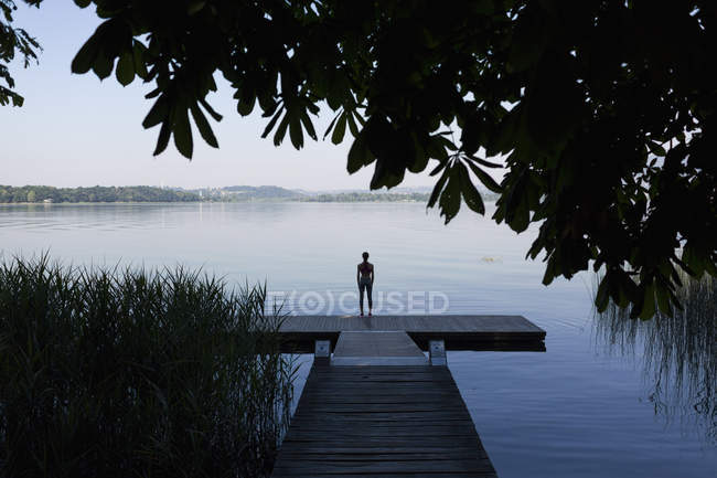 Young woman doing exercise at lake — Stock Photo