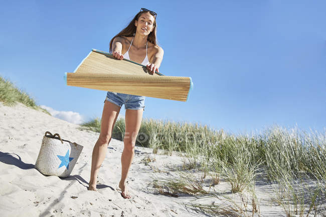Young woman with mat on the beach — Stock Photo