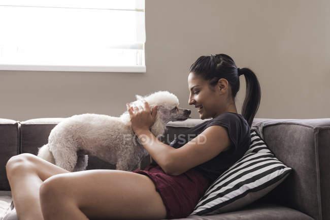 Молодая женщина дома ласкает свою собаку — стоковое фото