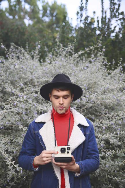 Man holding polaroid camera outdoors — Stock Photo