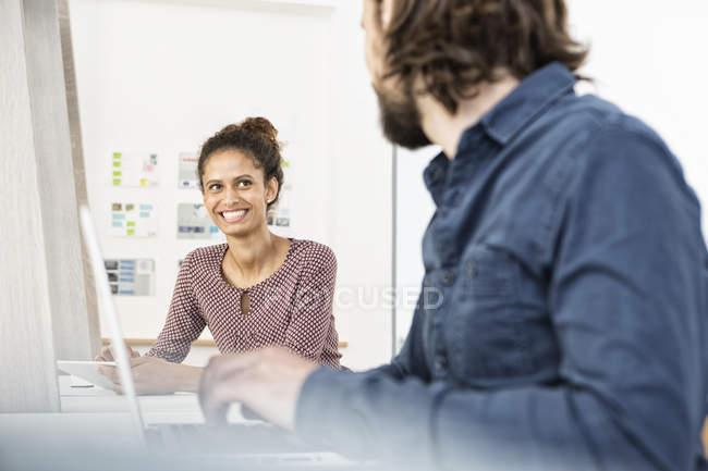 Femme souriante regardant un collègue au bureau — Photo de stock