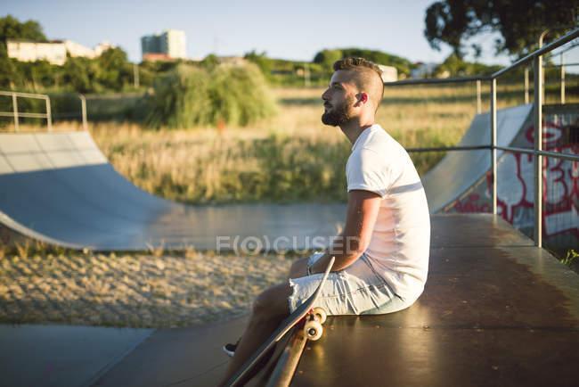 Nachdenklich sitzt auf der Rampe im Skatepark skateboarder — Stockfoto