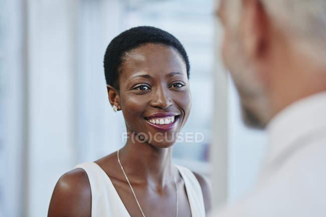 Mujer de negocios sonriente mirando a hombre de negocios - foto de stock