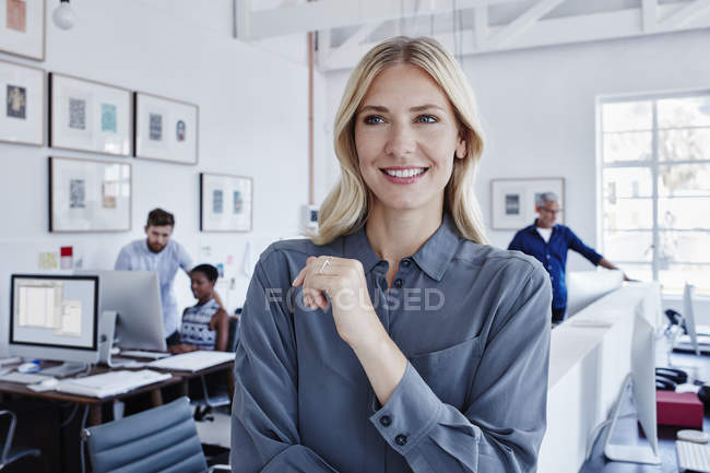 Smiling businesswoman in office with staff in background — Stock Photo