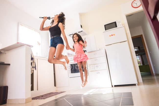 Juguetona adolescente con su hermana pequeña en la cocina fingiendo cantar en el micrófono - foto de stock