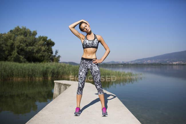 Jovem mulher fazendo exercício no lago — Fotografia de Stock