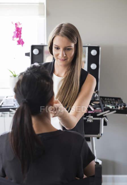 Visagiste styling customer in beauty salon — Stock Photo