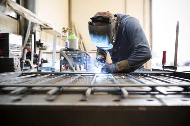 Soldador trabalhando com construção de metal na oficina — Fotografia de Stock