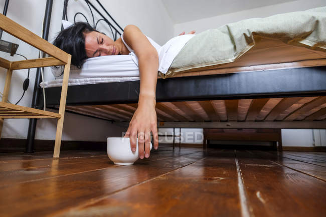 Tired woman lying in bed, hand on coffee cup — Stock Photo