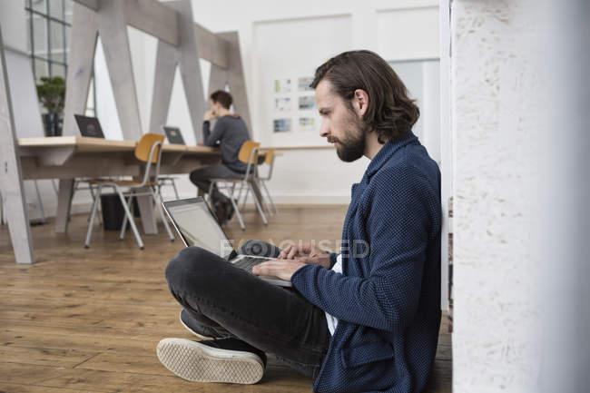Mann sitzt auf dem Boden im Büro und arbeitet am Laptop — Stockfoto