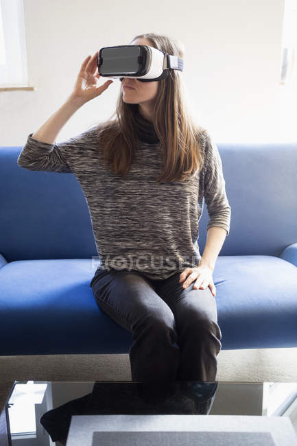 Woman sitting on couch wearing virtual reality glasses — Stock Photo