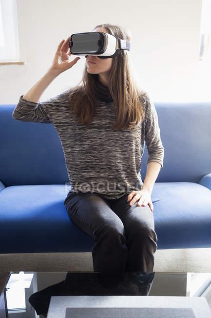 Mulher sentada no sofá usando óculos de realidade virtual — Fotografia de Stock