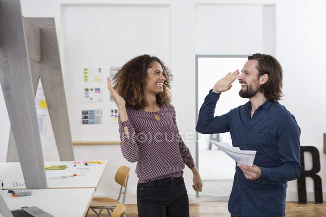Two happy colleagues in office high fiving — Stock Photo