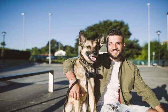Mann umarmt Hund im Skatepark und Blick in die Kamera — Stockfoto