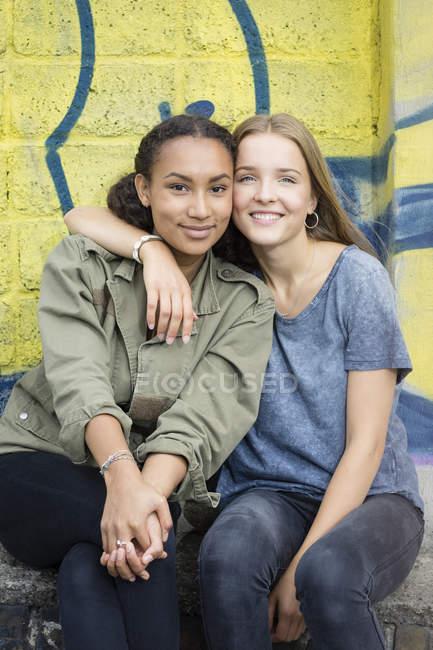 Portrait de deux adolescentes assises tête à tête devant des graffitis — Photo de stock