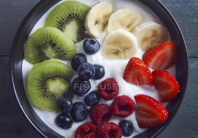Bowl of natural yoghurt with different fresh fruits and berries — Stock Photo