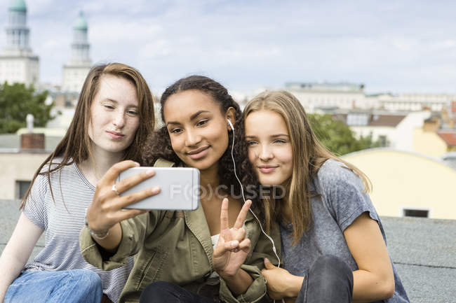 Germany, Berlin, three teenage girls sitting on roof top taking selfie with smartphone — Stock Photo