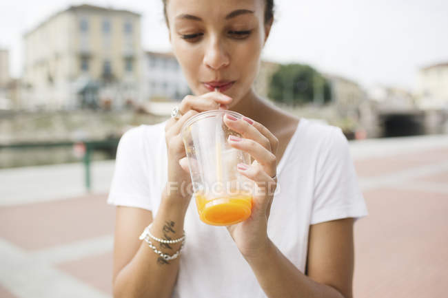Young woman drinking orange juice with straw — Stock Photo