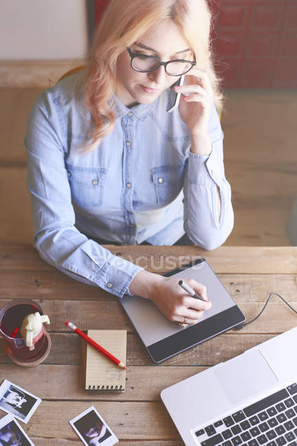 Illustrator working at home, using a graphics tablet and talking on phone — Stock Photo