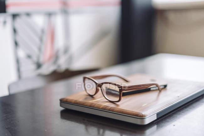 Ordinateur portable et lunettes en bois — Photo de stock