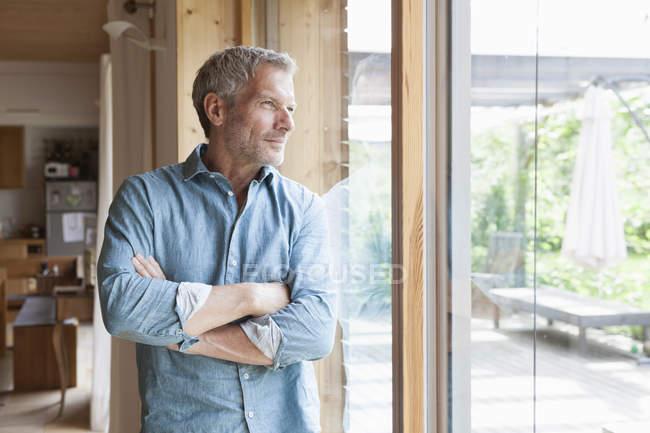 Homem maduro olhando pela janela — Fotografia de Stock