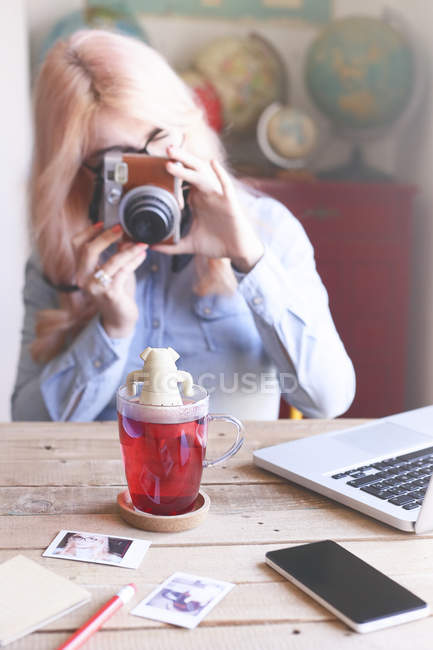 Photo prise femme de verre à thé avec caméra — Photo de stock