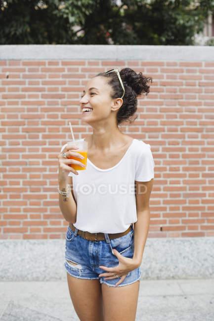 Молодая женщина с апельсиновым соком у кирпичной стены — стоковое фото