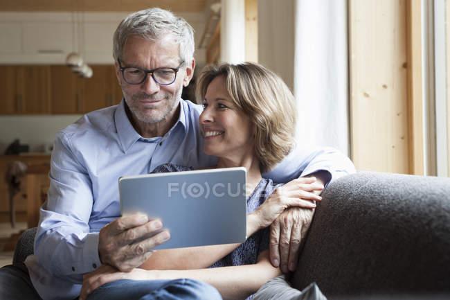 Älteres Paar teilen digital-Tablette auf couch — Stockfoto