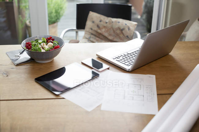 Desk with laptop and cell phone next to construction plan and salad — Stock Photo