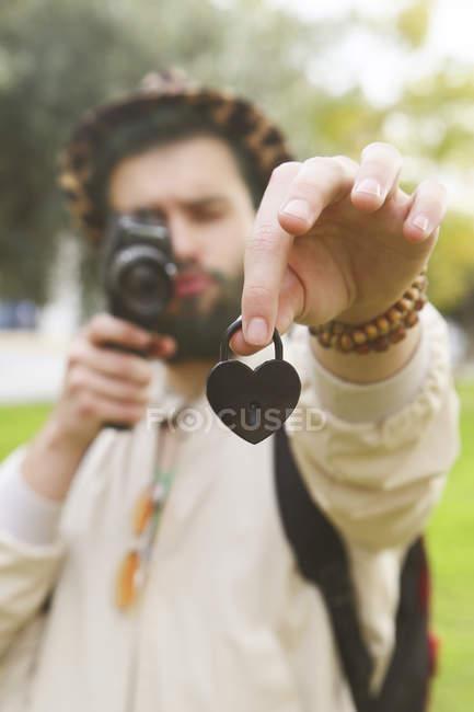 Homem gravando coração em forma de bloqueio de amor em sua mão com câmera de vídeo vintage — Fotografia de Stock