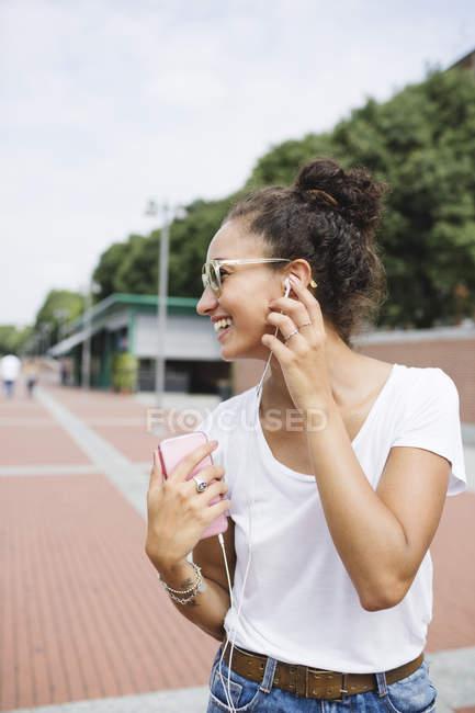 Giovane donna al telefono a piedi in città — Foto stock