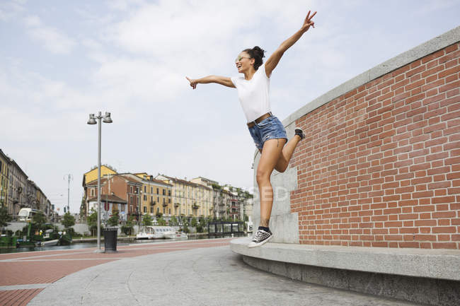 Young woman jumping by the built structure with arms outstretched — Stock Photo